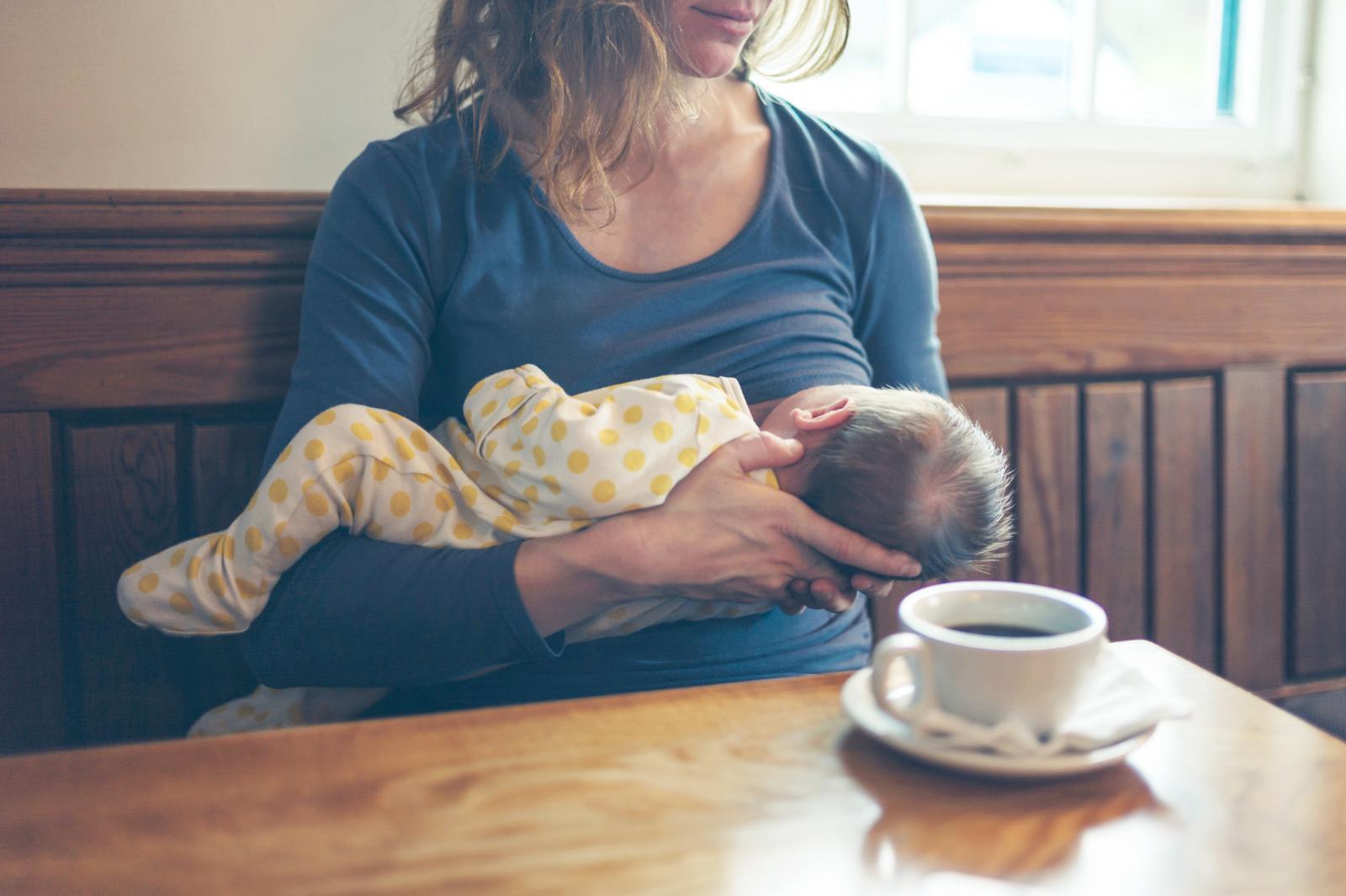 Mujer dando el pecho en un café