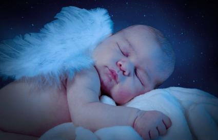 bebé con alas durmiendo en la cama