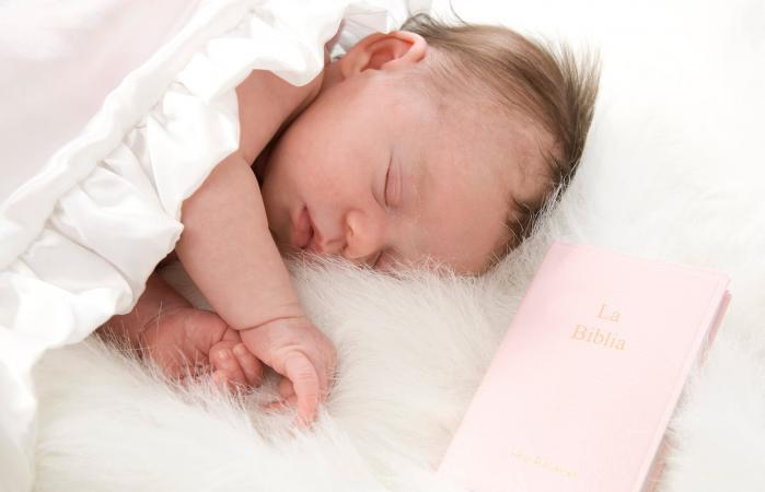 Bebé recién nacido durmiendo con la Biblia