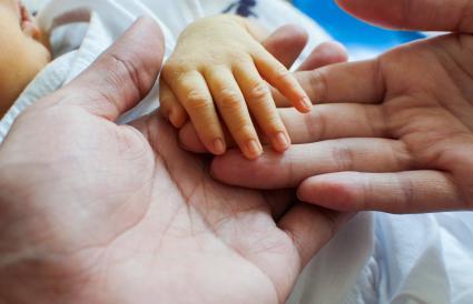 Un primer plano de la mano del padre y del bebé con la piel amarilla