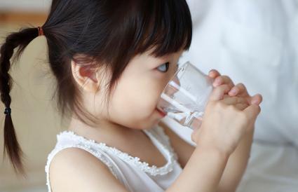 Bebé niña bebiendo un vaso de agua