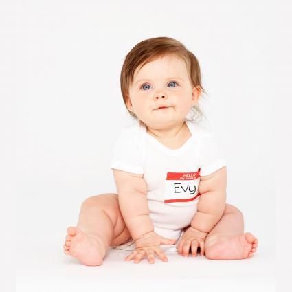 Bebé niña sentada con placa de identificación