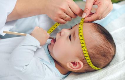 Pediatra midiendo la cabeza del bebé