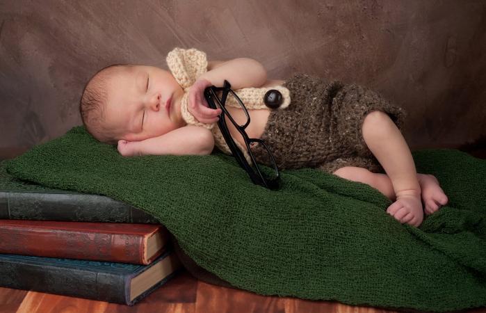 Bebé durmiendo sobre libros