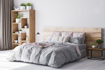 Cozy bedroom area at wooden apartment with wooden comfy bed and green plants.