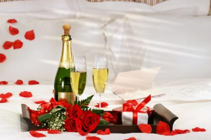 champagne, chocolates, rose petals on bed