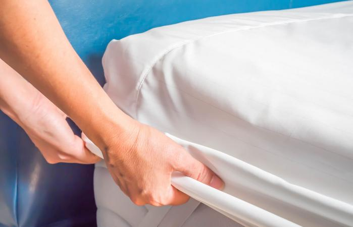 Woman putting the bedding cover on the bed