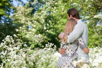 Couple hugging in field of flowers