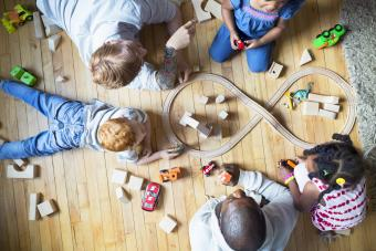 Fathers and children enjoying play date playing with toy train and wood blocks