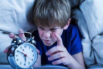 Grumpy boy turning off alarm clock