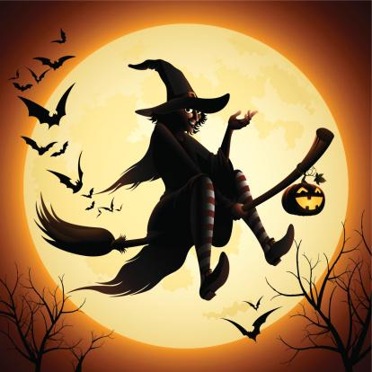 Witch riding a broom past the Halloween moon