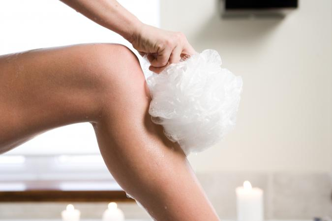 Woman washing her leg with poof