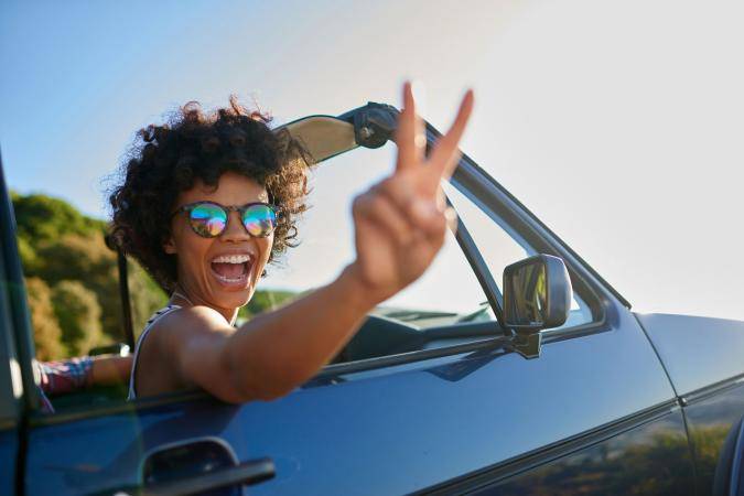 Woman in car flashing peace sign