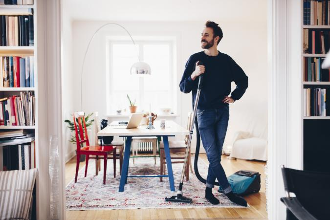 man vacuuming dining room