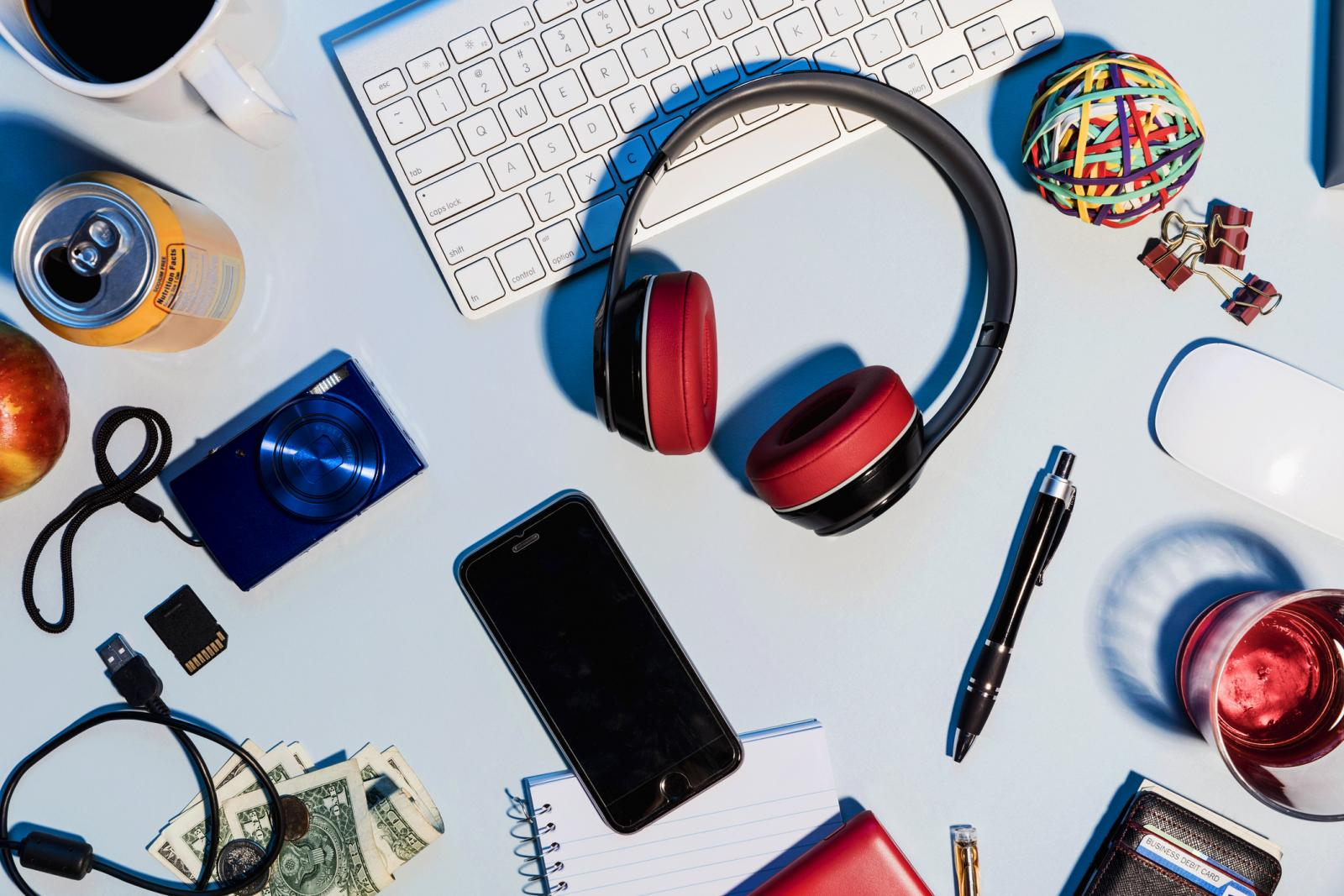 Headphones, smart phone, digital camera and office supplies on desk