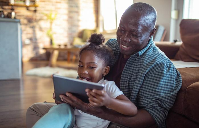 grandfather using a tablet with his granddaughter