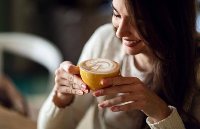 woman enjoying in cup of fresh coffee