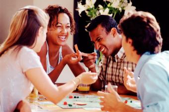 four adults playing board game