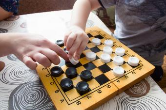 Woman and kid playing checkers at home