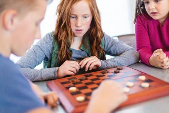 Three Siblings Playing checkers