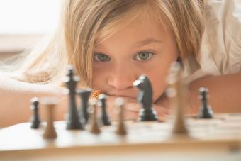 girl examining chess game board