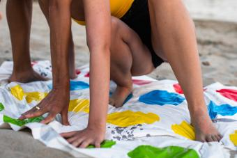 Young woman playing Twister at the beach