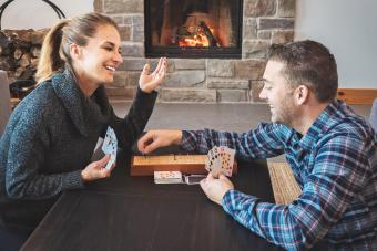 Couple playing cribbage in a warm home with fireplace