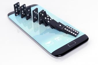 Black domino tiles falling in a row on smartphone screen
