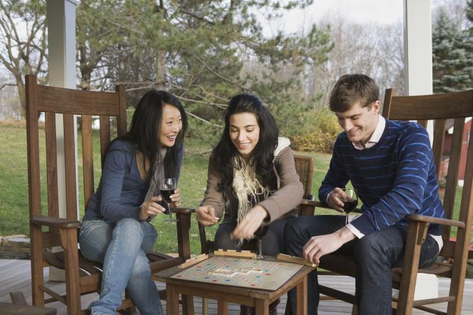 Friends playing scrabble on porch
