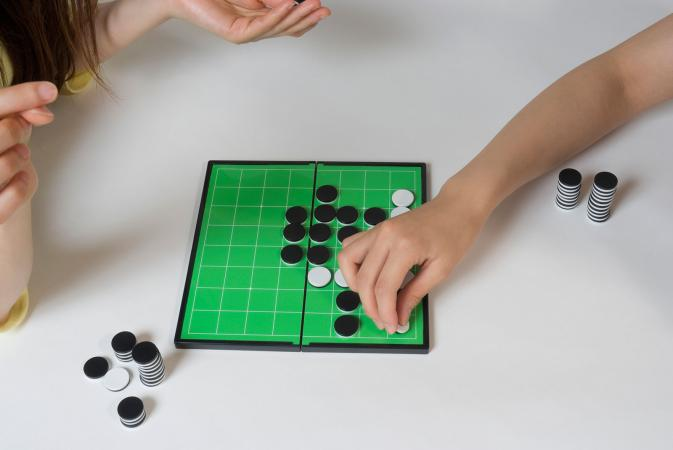 Two people playing Othello game