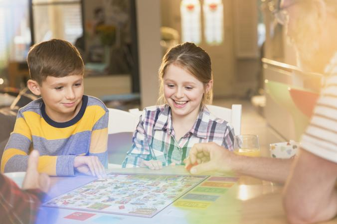 Father and children playing board game