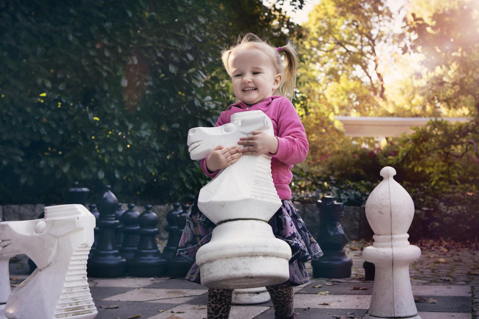 Girl playing with giant chess pieces
