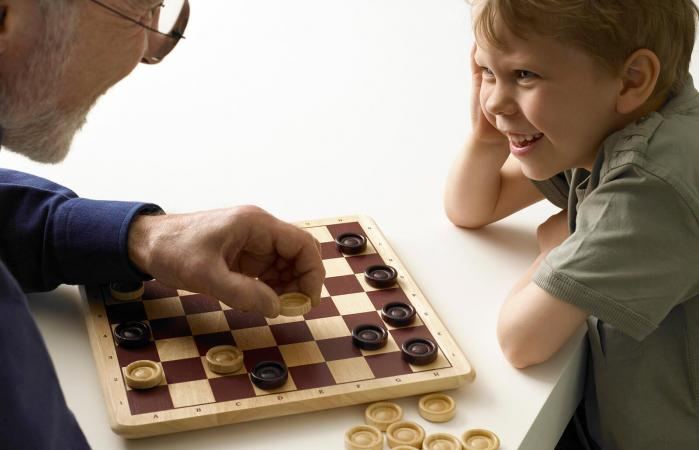 Boy playing checker with grandfather