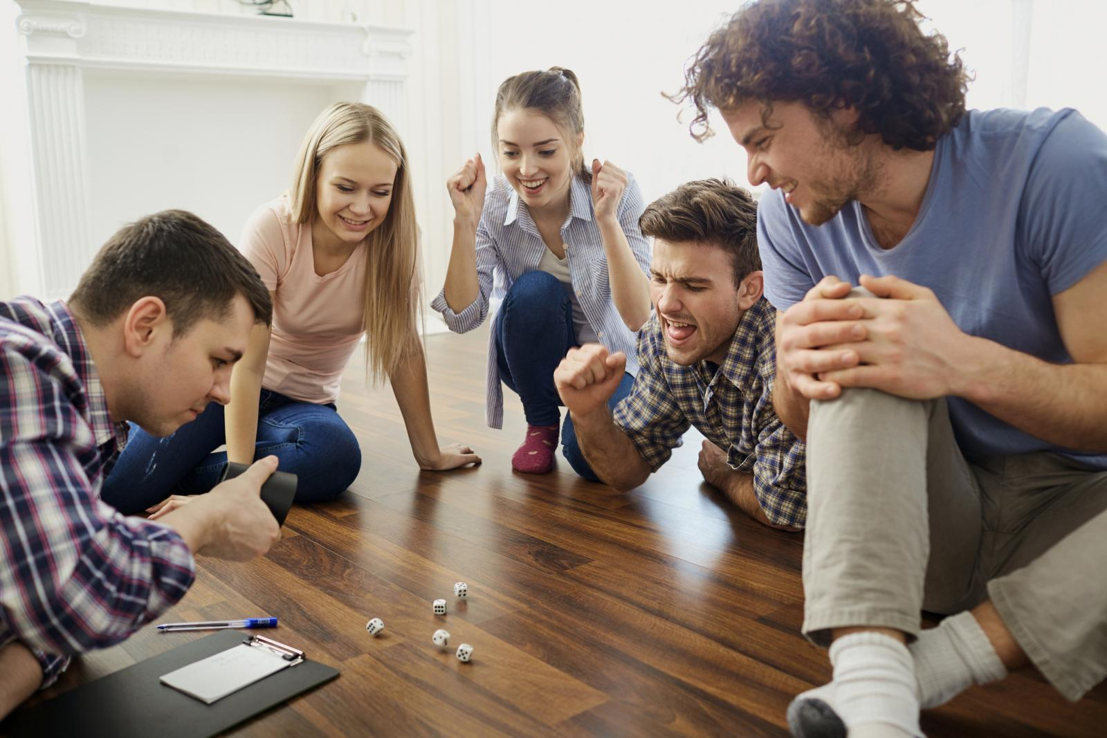A group of friends play board games on the floor indoors