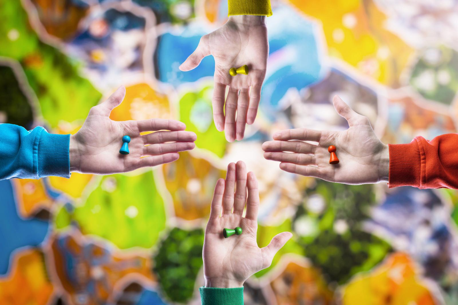 People holding in hand colourful playing figures on blurred board game field background