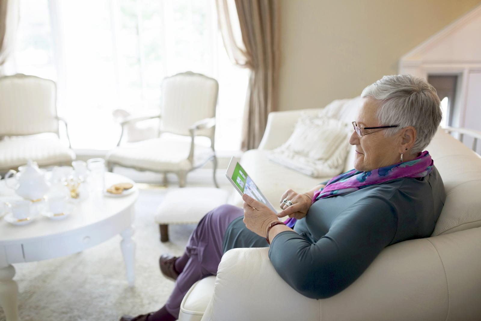 Senior woman using digital tablet on living room sofa