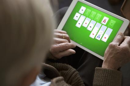 senior man playing solitaire on digital tablet