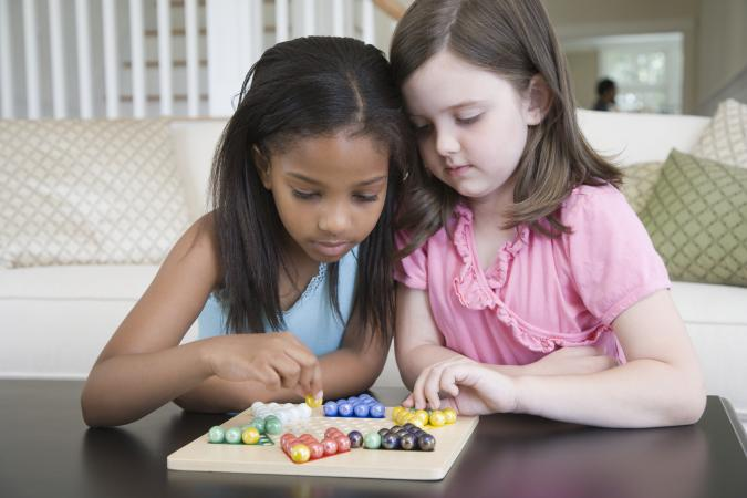 Two girls playing Chinese checkers