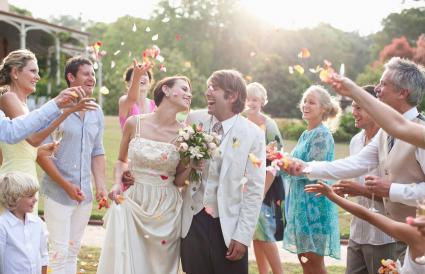 Invitados lanzando pétalos de rosas a pareja de recién casados