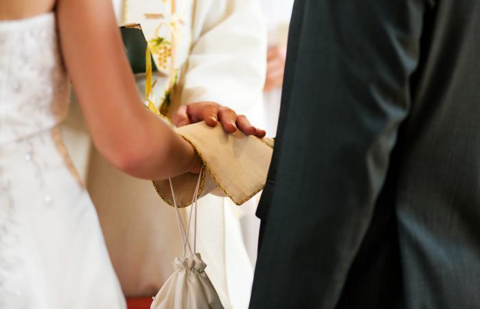 Pareja de novios recibiendo bendición del sacerdote