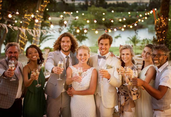 Pareja con invitados de la boda brindando