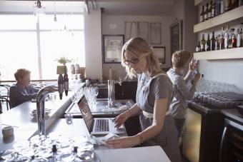 Family business owner working at laptop in cafe