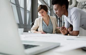 Businesswomen looking at blueprint in office building