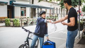 Food delivery woman giving package to male customer on sidewalk in city