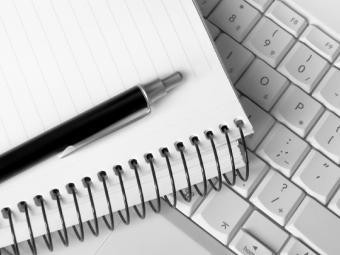 Spiral notebook, pen and computer keyboard