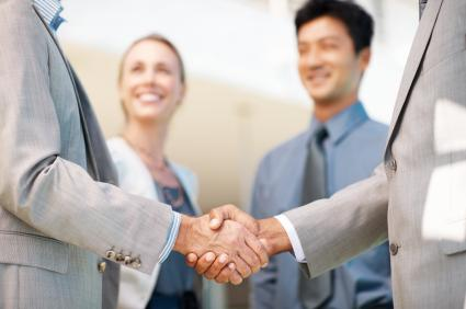 Western and Asian business people shaking hands