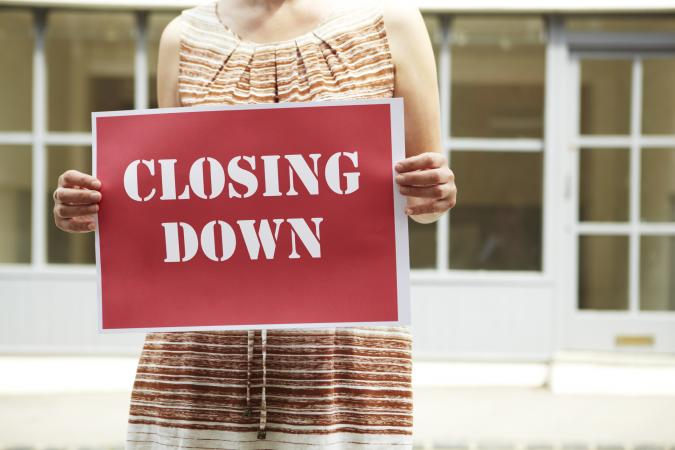 Woman Holding Closing Down Sign