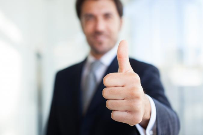 Businessman giving thumbs up