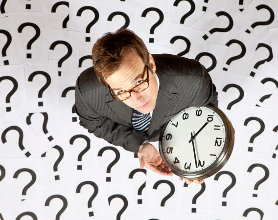Businessman looking up holding a clock