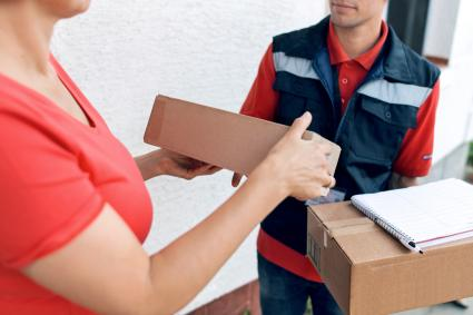 Woman accepting a delivery of boxes from deliveryman